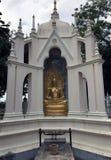 A estátua de bronze assentou a Buda na atitude do naga no arco da beleza Imagens de Stock