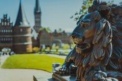 Estátua de bronze do leão na frente da porta de Holsten - Holstentor, uma porta da cidade que marca fora do limite ocidental do c Foto de Stock