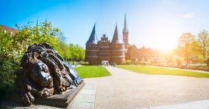 Estátua de bronze do leão na frente da porta de Holsten - tiro panorâmico de Holstentor e de parque, uma porta da cidade que marc Fotos de Stock