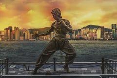 Estátua de Bruce Lee na avenida das estrelas Skyline sobre Victoria Harbour no fundo no por do sol imagens de stock royalty free