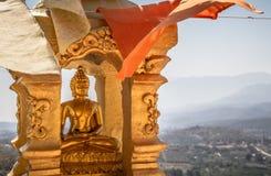 Estátua de buddha do ouro no rebaixo dourado com as bandeiras budistas e fundo brancos e alaranjados da montanha Imagens de Stock Royalty Free
