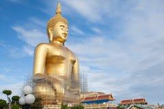 Estátua de buddha do ouro sob a construção no templo tailandês com céu claro WAT MUANG, Ang Thong, TAILÂNDIA Imagens de Stock Royalty Free