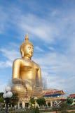 Estátua de buddha do ouro sob a construção no templo tailandês com céu claro WAT MUANG, Ang Thong, TAILÂNDIA Fotografia de Stock