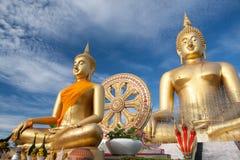 Estátua de buddha do ouro sob a construção no templo tailandês com céu claro WAT MUANG, Ang Thong, TAILÂNDIA Fotografia de Stock Royalty Free