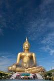 Estátua de buddha do ouro sob a construção no templo tailandês com céu claro WAT MUANG, Ang Thong, TAILÂNDIA Foto de Stock