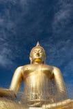 Estátua de buddha do ouro sob a construção no templo tailandês com céu claro WAT MUANG, Ang Thong, TAILÂNDIA Fotos de Stock