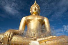 Estátua de buddha do ouro sob a construção no templo tailandês com céu claro WAT MUANG, Ang Thong, TAILÂNDIA Imagem de Stock Royalty Free