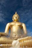 Estátua de buddha do ouro sob a construção no templo tailandês com céu claro WAT MUANG, Ang Thong, TAILÂNDIA Foto de Stock Royalty Free