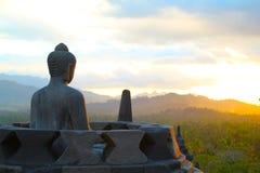Estátua de Buddha que olha o por do sol sobre o templo de Borobodur Imagem de Stock Royalty Free