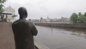 Estátua de buddha rezando no cais do rio de Vltava em Praga no dia nebuloso, vista traseira video estoque