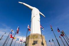 Estátua de Cristo del Rey de Cali com bandeiras do mundo e o céu azul, colo fotos de stock
