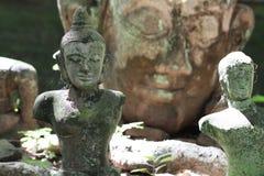 A estátua de pedra antiga arruinada de buddha na frente do papel de parede enorme da estátua da cabeça de buddha, arte corporal q Imagem de Stock
