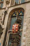 Estátua de pedra do leão com protetor colorido e a janela vitrificada que decoram a fachada gótico da câmara municipal no Gouda Fotografia de Stock Royalty Free