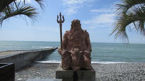 A estátua de Poseidon na terraplenagem do beira-mar em Sochi, Rússia do sul O Mar Negro, palmeiras, Pebble Beach imagem de stock