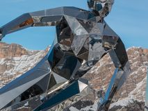 Estátua de prata do esquiador, escultura feita com espelhos e cumes italianos das dolomites no fundo Fotografia de Stock Royalty Free