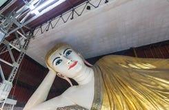 Estátua de reclinação grande de buddha Kyauk Htat Gyi buddha em Myanmar Burma na noite Imagem de Stock
