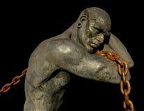 Estátua de um escravo que leva um barco usando uma corrente fotos de stock royalty free