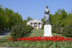 Estátua de um fazendeiro coletivo em um suporte O legado da era soviética Uma cama de flor com tulipas e as árvores novas dentro Fotografia de Stock Royalty Free