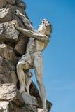 Estátua de um homem que escala uma rocha Imagem de Stock Royalty Free