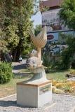 A estátua de um peixe dourado montou em um suporte na margem dentro Imagens de Stock