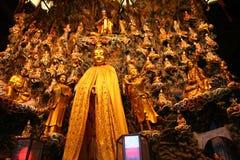 Estátua do deus do ouro cercada por estátuas douradas das crianças imagens de stock