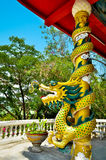 Estátua do dragão do estilo chinês envolvida em torno do polo vermelho e da arte Chin Fotografia de Stock Royalty Free