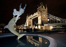Estátua do golfinho e ponte da torre, na noite Londres. fotografia de stock royalty free