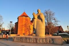 Estátua do granito do papa John XXIII com a igreja católica romana de St Marcin na parte traseira wroclaw imagem de stock