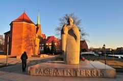 Estátua do granito do papa John XXIII com a igreja católica romana de St Marcin na parte traseira wroclaw fotos de stock