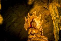 Estátua dourada da Buda com a estátua grande da serpente na caverna Imagem de Stock Royalty Free