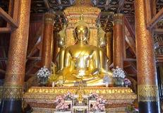 Estátua dourada da Buda na atitude de conter Mara no templo de Wat Phumin Phumin, província de Nan, Tailândia fotos de stock royalty free