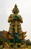 Estátua gigante do guardião que está na frente da montanha com b branco Fotos de Stock Royalty Free