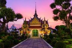 Estátua gigante no pagode branco em Wat Arun Ratchawararam Ratchawaramahawihan no tempo do por do sol Imagens de Stock