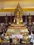 estátua Ouro-colorida da Buda e das monges no templo budista Fotografia de Stock