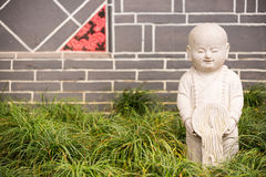 Estátua pequena da pedra de buddha na grama com uma parede de tijolo no CCB Foto de Stock Royalty Free
