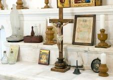 Estátua pequena de Jesus Christ na cruz, cercada por vários objetos em uma igreja pequena em Masseria IL Frantoio, Itália do sul foto de stock
