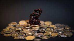Estátua pequena do elefante em uma pilha das moedas Foto de Stock Royalty Free