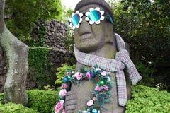 Estátua tradicional de Harubang da ilha de Jeju decorada com flores, óculos de sol, e lenço em Camellia Hill, Coreia do Sul foto de stock royalty free