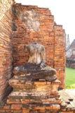 Estátua velha da Buda e tijolos alaranjados no templo de Chaiwatthanaram Imagem de Stock