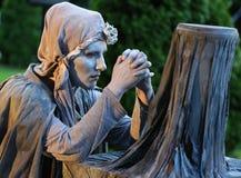Estátua viva - rezar da mulher Imagem de Stock