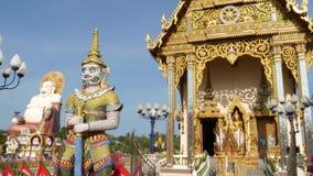 Estátuas coloridas perto do templo asiático Templo budista decorativo no dia ensolarado no país oriental Estátua de Hotei fora video estoque