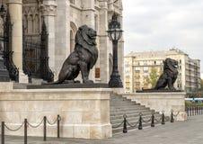 Estátuas de bronze do leão que flanqueiam a entrada do leste da construção húngara do parlamento, Budapest imagem de stock royalty free