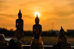 Estátuas de buddha da silhueta no fundo borrado do por do sol tailândia Foto de Stock