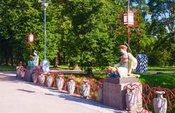 Estátuas pintadas do chinês com grandes luzes nos polos que sentam-se na ponte chinesa grande em Alexander Park, Tsarskoye Selo, Imagens de Stock