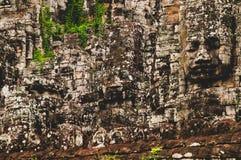 estátuas principais de pedra Líquene-cobertas em Angkor Wat, Siem Reap, Camboja, Indochina, Ásia - cara sobre na cor fotografia de stock royalty free