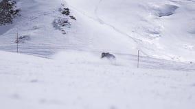Estância de esqui O passeio do Snowboarder na inclinação, quebra abruptamente Pulverizador da neve Dia ensolarado video estoque