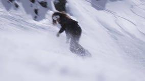 Estância de esqui O passeio do Snowboarder na inclinação, quebra abruptamente Pulverizador da neve Paisagem filme