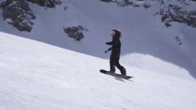 Estância de esqui O passeio feliz do snowboarder na inclinação, quebra abruptamente Pulverizador da neve Sun video estoque