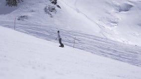 Estância de esqui Passeio do Snowboarder na inclinação velocidade Montanhas brancas Dia ensolarado filme