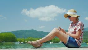 A estância turística satisfeita aprecia um smartphone No fundo, nas montanhas e no lago spain vídeos de arquivo